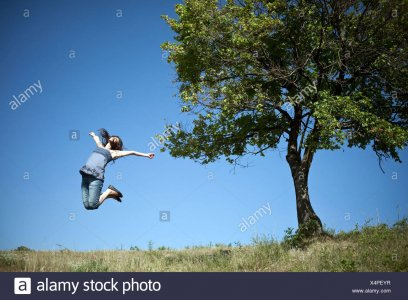 woman-jumping-by-tree-X4PEYR.jpg